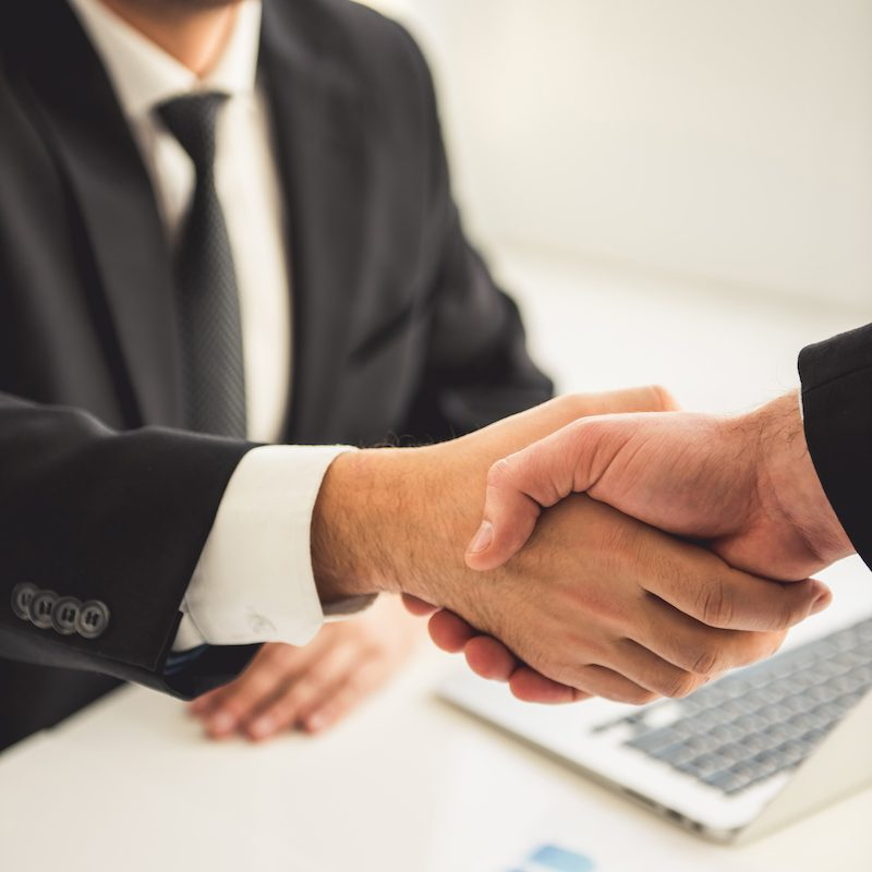 Cropped image of handsome businessman in suit shaking partner's hand and smiling while working in office